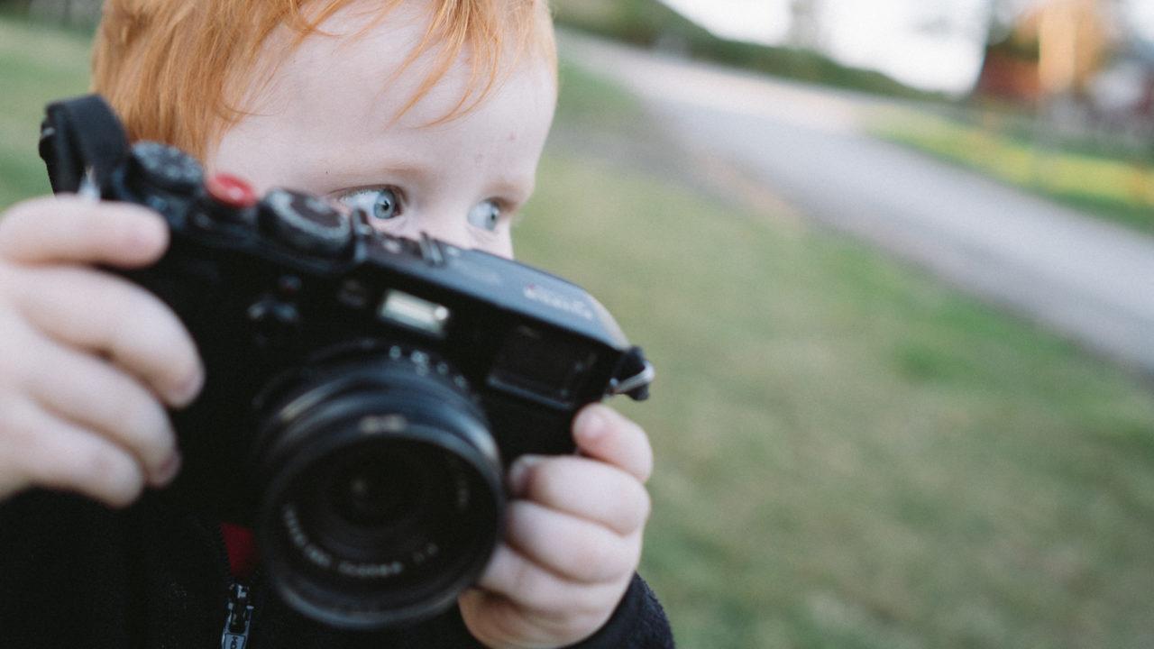 Gutt med kamera ser etter motiver å fotografere.