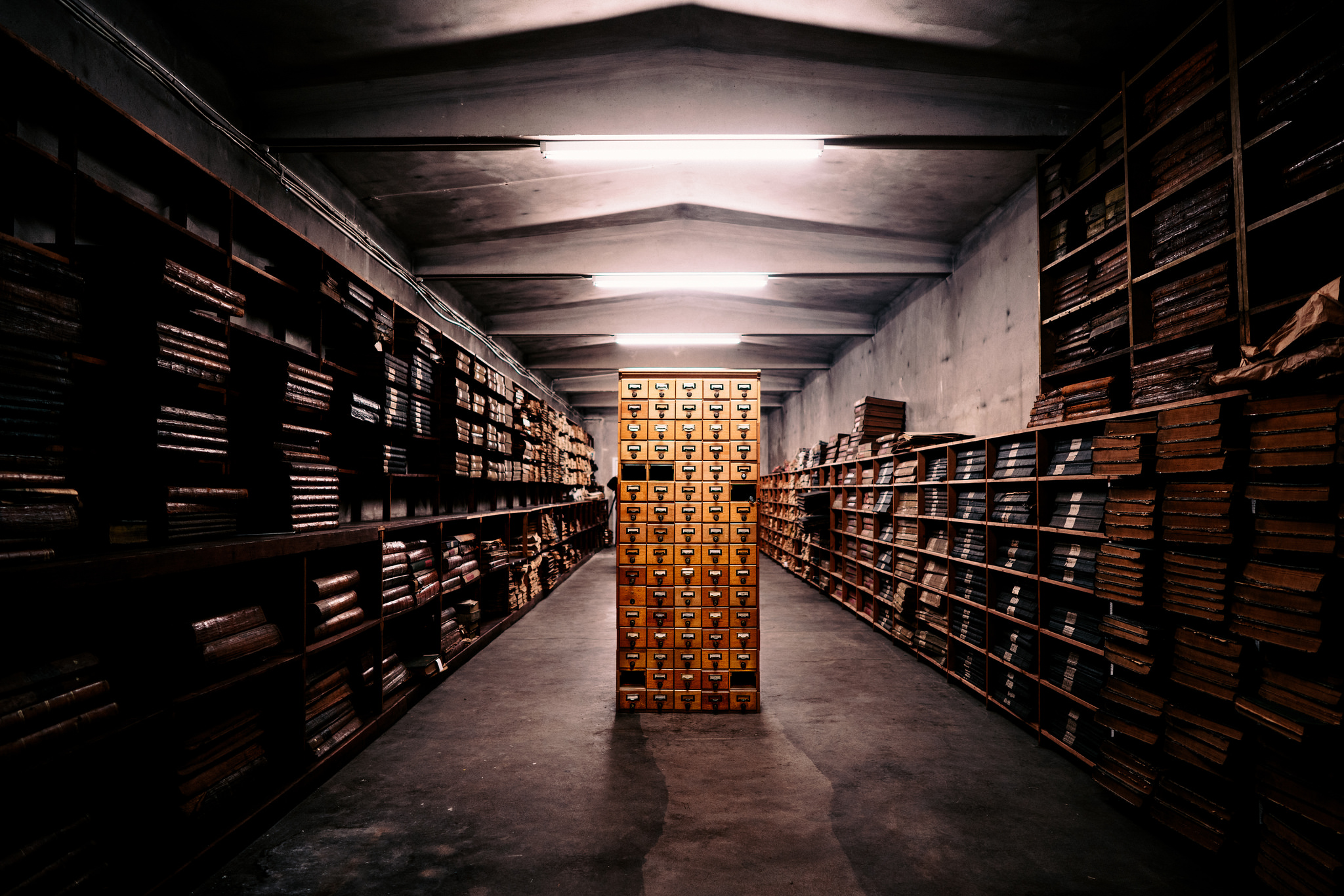 Bilde av et arkivskap og massevis av stabler med papirer.