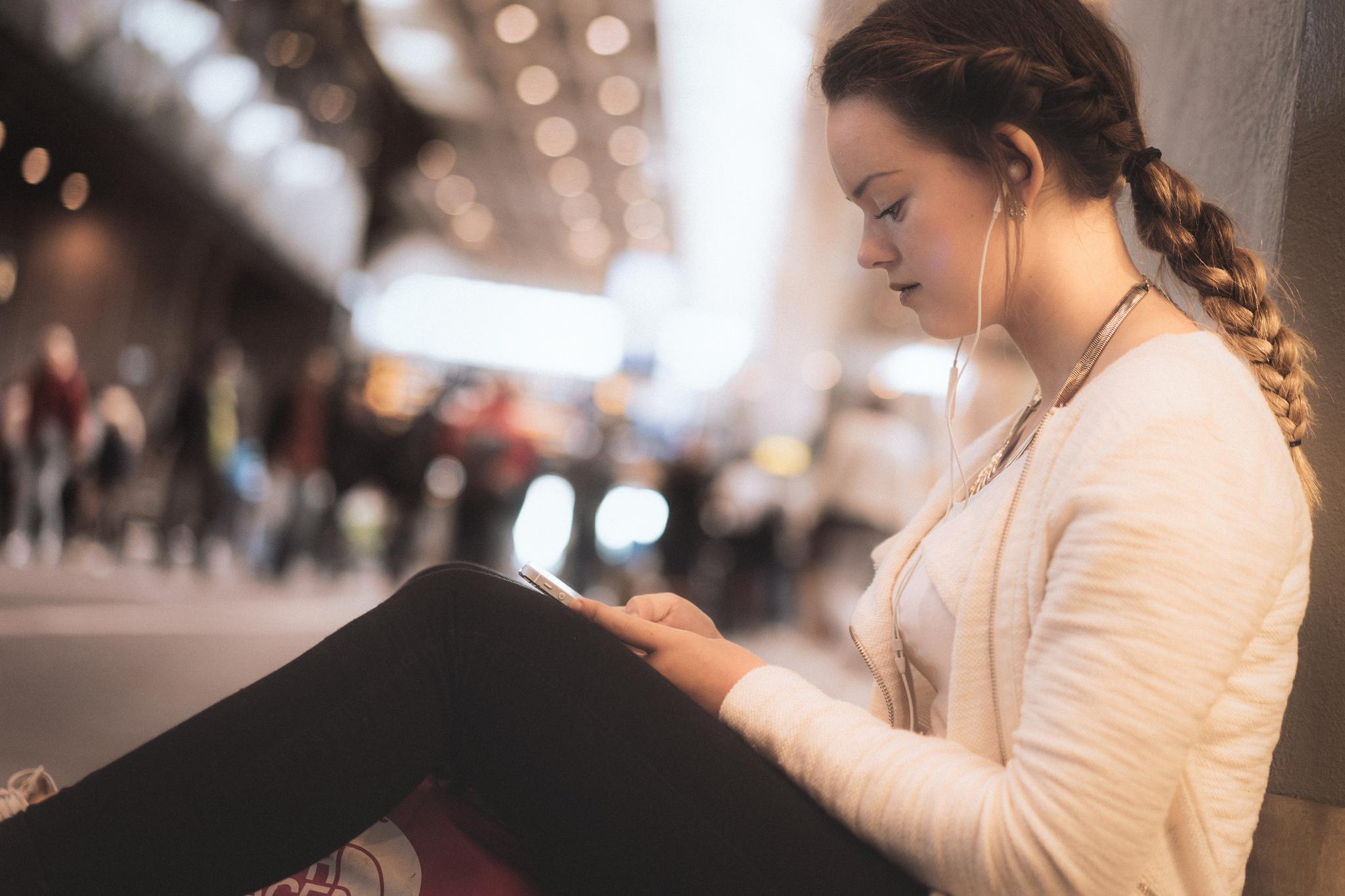 Foto av ung kvinne med mobilen sin på Oslo S.